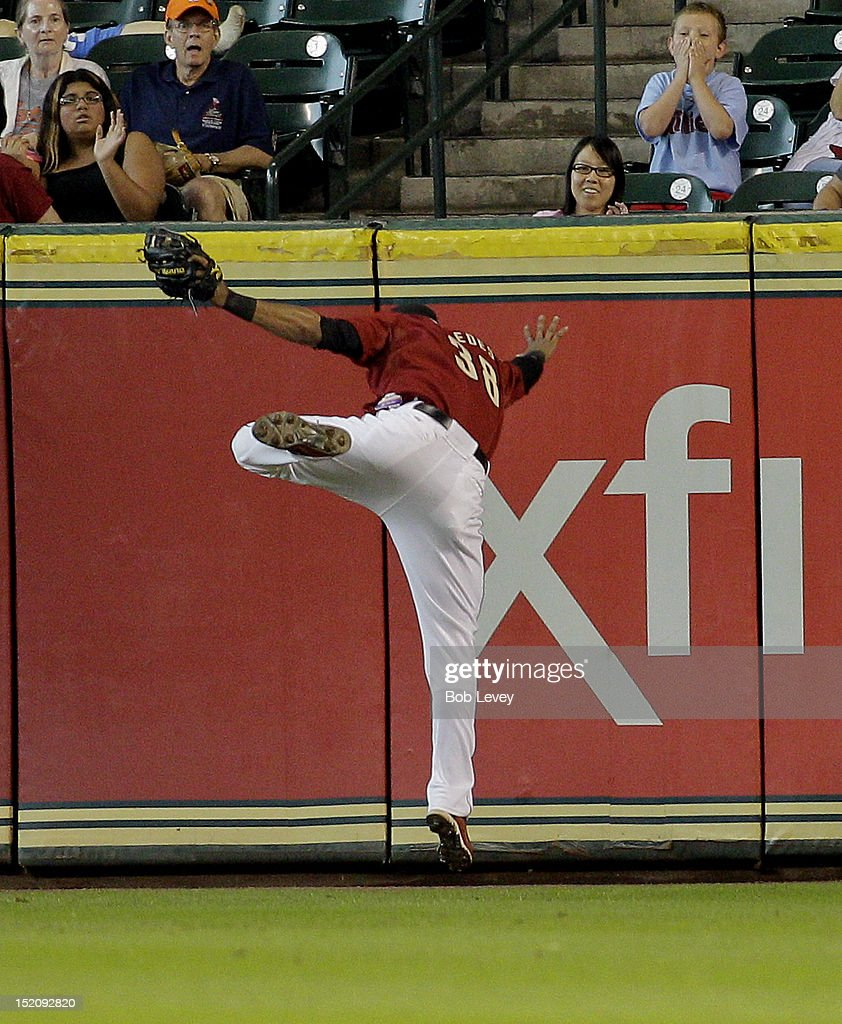 Jimmy Paredes #38 of the Houston Astros makes a leaping catch at the wall off a fly ball by Chase Utley #26 of the Philadelphia Phillies in the seventh inning at Minute Maid Park on September 16, 2012 in Houston, Texas.