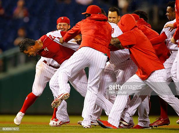 Jimmy Paredes of the Philadelphia Phillies is mobbed by teammates after hitting the game winning single in the 13th inning defeating the Miami...