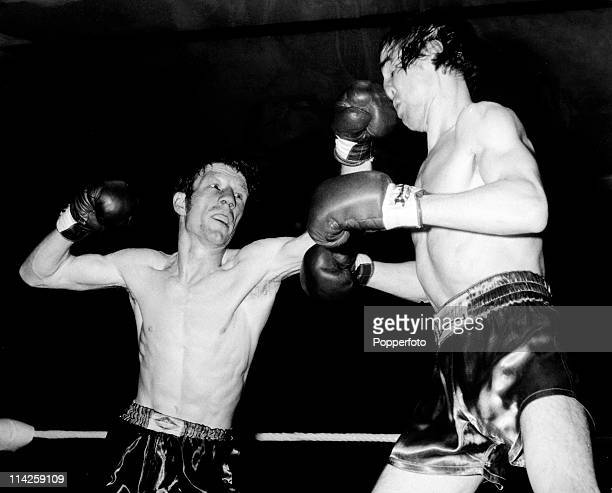 Jimmy Revie receives a smashing left hook from Evan Armstrong during their British featherweight title fight at the Grosvenor House Hotel London on...