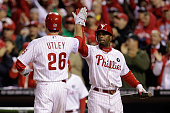 Jimmy Rollins and Chase Utley of the Philadelphia Phillies celebrate after scoring on a Ryan Howard RBI single in the first inning against the St...