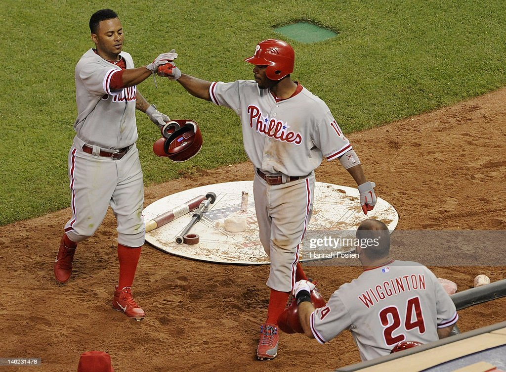 <a gi-track='captionPersonalityLinkClicked' href=/galleries/search?phrase=Jimmy+Rollins&family=editorial&specificpeople=204478 ng-click='$event.stopPropagation()'>Jimmy Rollins</a> #11 and Michael Martinez #7 of the Philadelphia Phillies celebrate scoring against the Minnesota Twins during the sixth inning as <a gi-track='captionPersonalityLinkClicked' href=/galleries/search?phrase=Ty+Wigginton&family=editorial&specificpeople=211533 ng-click='$event.stopPropagation()'>Ty Wigginton</a> #24 looks on in the dugout during the game on June 12, 2012 at Target Field in Minneapolis, Minnesota.
