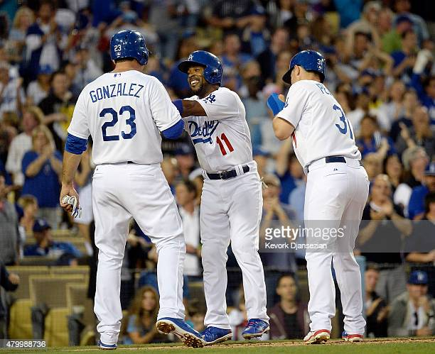 Jimmy Rollins of the Los Angeles Dodgers celebrates his three run home run with Adrian Gonzalez and Joc Pederson against Philadelphia Phillies during...
