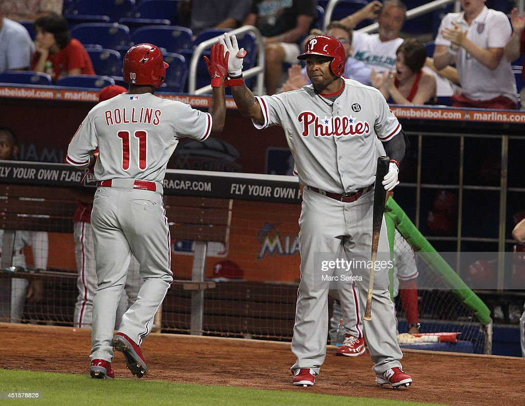 Jimmy Rollins #11 (L) of the Philadelphia Phillies celebrates scoring a run with a teammate against the Miami Marlins during the first inning at Marlins Park on July 1, 2014 in Miami, Florida.