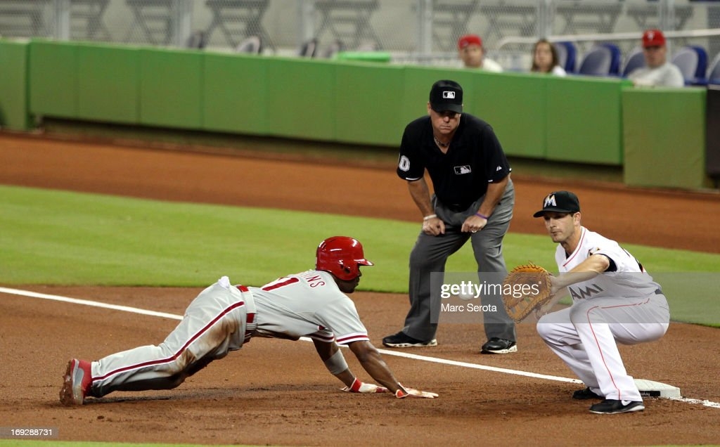 <a gi-track='captionPersonalityLinkClicked' href=/galleries/search?phrase=Jimmy+Rollins&family=editorial&specificpeople=204478 ng-click='$event.stopPropagation()'>Jimmy Rollins</a> #11 of the Philadelphia Phillies dives into first base during a pick off attempt in the first inning by First baseman <a gi-track='captionPersonalityLinkClicked' href=/galleries/search?phrase=Nick+Green+-+Baseball+Player&family=editorial&specificpeople=15937635 ng-click='$event.stopPropagation()'>Nick Green</a> #22 of the Miami Marlins at Marlins Park on May 22, 2013 in Miami, Florida.