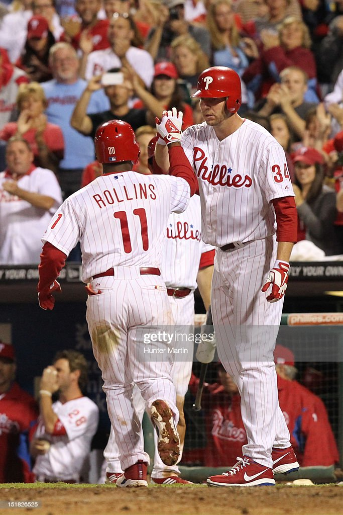 <a gi-track='captionPersonalityLinkClicked' href=/galleries/search?phrase=Jimmy+Rollins&family=editorial&specificpeople=204478 ng-click='$event.stopPropagation()'>Jimmy Rollins</a> #11 of the Philadelphia Phillies is congratulated by starting pitcher <a gi-track='captionPersonalityLinkClicked' href=/galleries/search?phrase=Roy+Halladay&family=editorial&specificpeople=208782 ng-click='$event.stopPropagation()'>Roy Halladay</a> #34 after hitting a home run during a game against the Miami Marlins at Citizens Bank Park on September 11, 2012 in Philadelphia, Pennsylvania. The Phillies won 9-7.