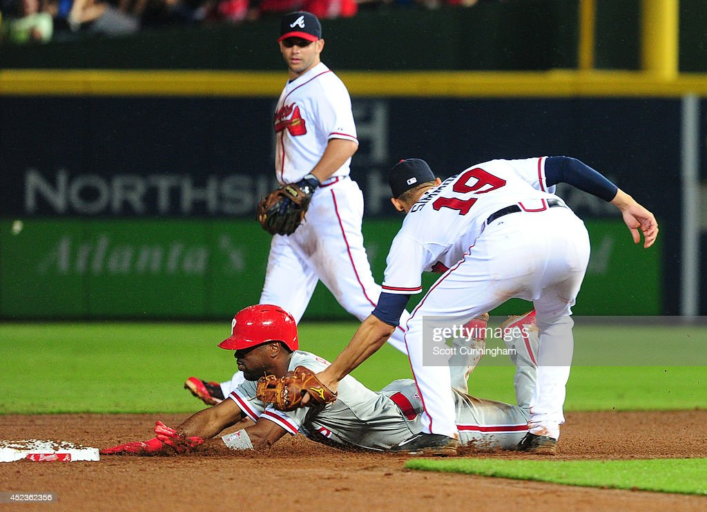 <a gi-track='captionPersonalityLinkClicked' href=/galleries/search?phrase=Jimmy+Rollins&family=editorial&specificpeople=204478 ng-click='$event.stopPropagation()'>Jimmy Rollins</a> #11 of the Philadelphia Phillies is tagged out at second base by <a gi-track='captionPersonalityLinkClicked' href=/galleries/search?phrase=Andrelton+Simmons&family=editorial&specificpeople=8978424 ng-click='$event.stopPropagation()'>Andrelton Simmons</a> #19 of the Atlanta Braves during the eighth inning at Turner Field on July 18, 2014 in Atlanta, Georgia.