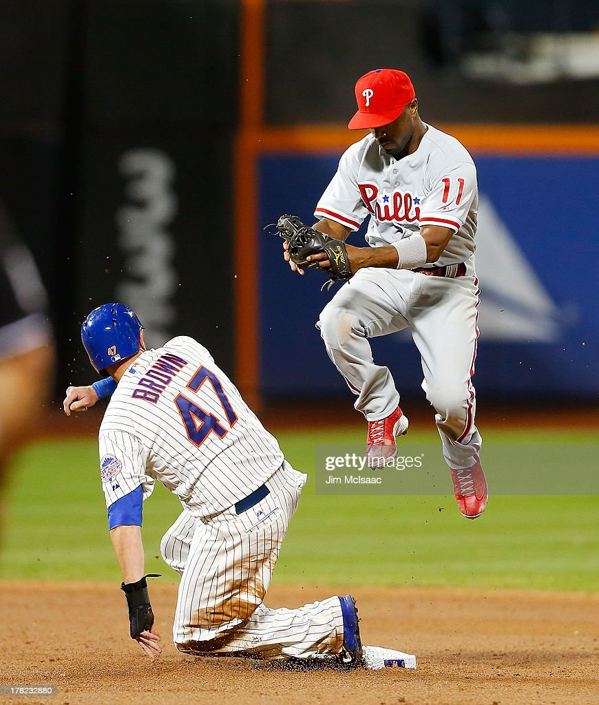 <a gi-track='captionPersonalityLinkClicked' href=/galleries/search?phrase=Jimmy+Rollins&family=editorial&specificpeople=204478 ng-click='$event.stopPropagation()'>Jimmy Rollins</a> #11 of the Philadelphia Phillies leaps after missing a ball thrown for an error by first baseman Kevin Frandsen #28 (not pictured) allowing Andrew Brown #47 of the New York Mets to advance to third base during the sixth inning at Citi Field on August 27, 2013 in the Flushing neighborhood of the Queens borough of New York City.