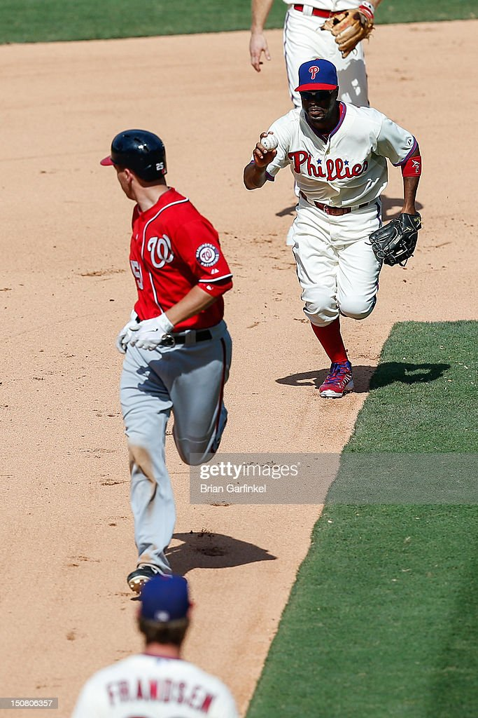 <a gi-track='captionPersonalityLinkClicked' href=/galleries/search?phrase=Jimmy+Rollins&family=editorial&specificpeople=204478 ng-click='$event.stopPropagation()'>Jimmy Rollins</a> #11 of the Philadelphia Phillies runs down <a gi-track='captionPersonalityLinkClicked' href=/galleries/search?phrase=Adam+LaRoche&family=editorial&specificpeople=216533 ng-click='$event.stopPropagation()'>Adam LaRoche</a> #25 of the Washington Nationals in the seventh inning of the game at Citizens Bank Park on August 26, 2012 in Philadelphia, Pennsylvania. The Phillies won 4-1.