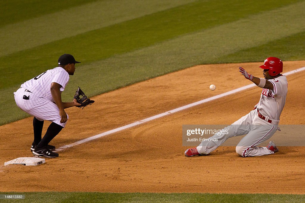 <a gi-track='captionPersonalityLinkClicked' href=/galleries/search?phrase=Jimmy+Rollins&family=editorial&specificpeople=204478 ng-click='$event.stopPropagation()'>Jimmy Rollins</a> #11 of the Philadelphia Phillies slides in for a triple as third baseman Chris Nelson #10 of the Colorado Rockies fields the throw during the eighth inning at Coors Field on July 13, 2012 in Denver, Colorado. The Rockies defeated the Phillies 6-2.