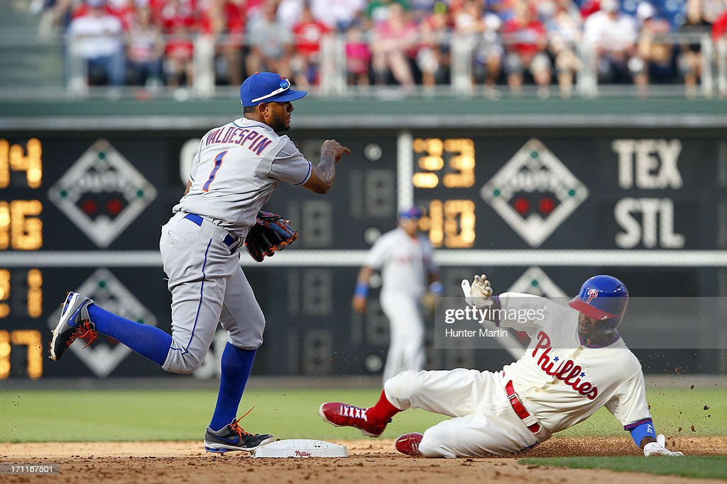 Jimmy Rollins #11 of the Philadelphia Phillies slides into second base as Jordany Valdespin #1 of the New York Mets turns a double-play during a game at Citizens Bank Park on June 22, 2013 in Philadelphia, Pennsylvania. The Phillies won 8-7.
