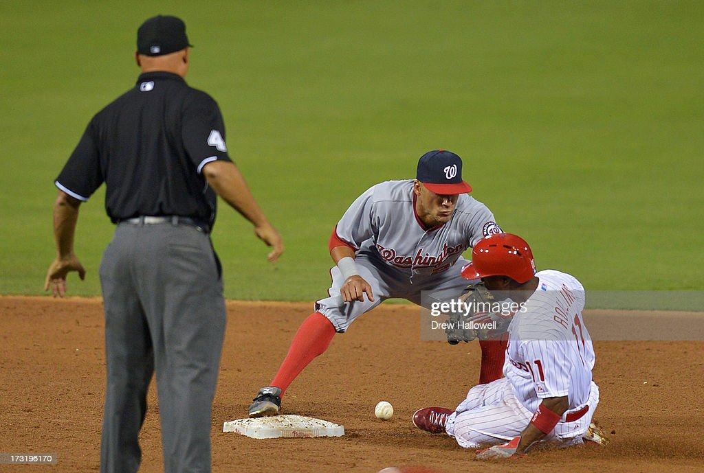 <a gi-track='captionPersonalityLinkClicked' href=/galleries/search?phrase=Jimmy+Rollins&family=editorial&specificpeople=204478 ng-click='$event.stopPropagation()'>Jimmy Rollins</a> #11 of the Philadelphia Phillies slides safe into second base on an error as <a gi-track='captionPersonalityLinkClicked' href=/galleries/search?phrase=Ian+Desmond&family=editorial&specificpeople=835572 ng-click='$event.stopPropagation()'>Ian Desmond</a> #20 of the Washington Nationals tries catch the ball at Citizens Bank Park on July 9, 2013 in Philadelphia, Pennsylvania. The Phillies won 4-2.