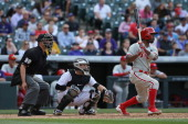 Jimmy Rollins of the Philadelphia Phillies takes an at bat as catcher Jordan Pacheco of the Colorado Rockies backs up the plate and umpire Chris...
