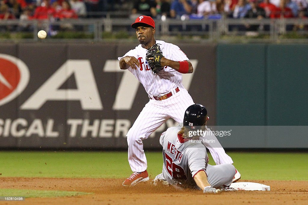 Jimmy Rollins #11 of the Philadelphia Phillies throws to first base as Jayson Werth #28 slides into second during a game against the Washington Nationals at Citizens Bank Park on September 26, 2012 in Philadelphia, Pennsylvania.