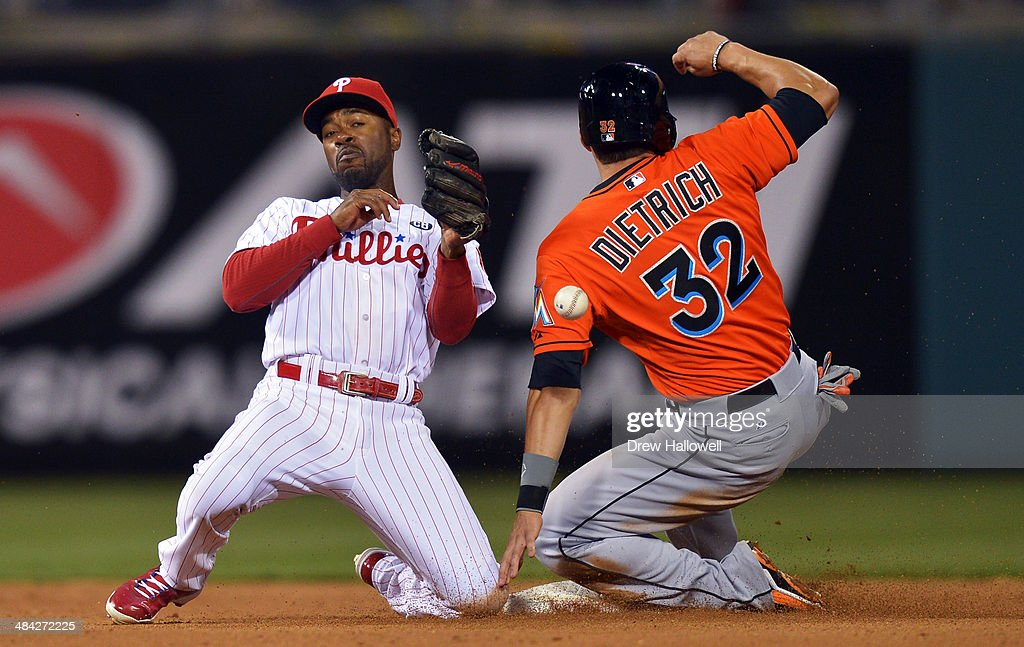 <a gi-track='captionPersonalityLinkClicked' href=/galleries/search?phrase=Jimmy+Rollins&family=editorial&specificpeople=204478 ng-click='$event.stopPropagation()'>Jimmy Rollins</a> #11 of the Philadelphia Phillies tries to catch the ball as <a gi-track='captionPersonalityLinkClicked' href=/galleries/search?phrase=Derek+Dietrich&family=editorial&specificpeople=10507746 ng-click='$event.stopPropagation()'>Derek Dietrich</a> #32 of the Miami Marlins slides safely into second on a steal at Citizens Bank Park on April 11, 2014 in Philadelphia, Pennsylvania. The Phillies won 6-3.
