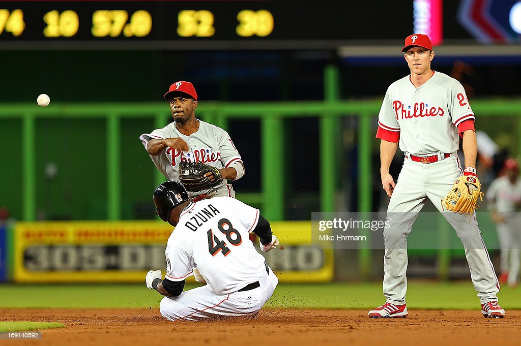 <a gi-track='captionPersonalityLinkClicked' href=/galleries/search?phrase=Jimmy+Rollins&family=editorial&specificpeople=204478 ng-click='$event.stopPropagation()'>Jimmy Rollins</a> #11 of the Philadelphia Phillies turns a double play as <a gi-track='captionPersonalityLinkClicked' href=/galleries/search?phrase=Marcell+Ozuna&family=editorial&specificpeople=10358366 ng-click='$event.stopPropagation()'>Marcell Ozuna</a> #48 of the Miami Marlins slides into second during a game at Marlins Park on May 20, 2013 in Miami, Florida.