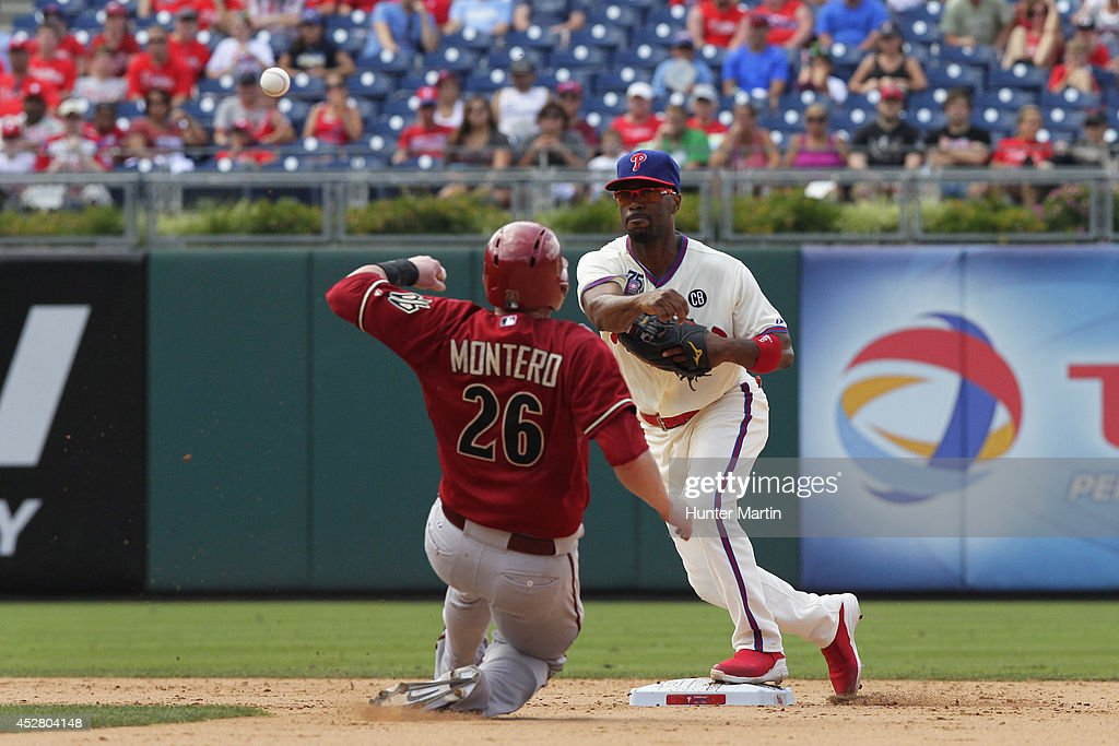 <a gi-track='captionPersonalityLinkClicked' href=/galleries/search?phrase=Jimmy+Rollins&family=editorial&specificpeople=204478 ng-click='$event.stopPropagation()'>Jimmy Rollins</a> #11 of the Philadelphia Phillies turns a game ending double-play as catcher <a gi-track='captionPersonalityLinkClicked' href=/galleries/search?phrase=Miguel+Montero&family=editorial&specificpeople=836495 ng-click='$event.stopPropagation()'>Miguel Montero</a> #26 of the Arizona Diamondbacks slides into second base in the ninth inning during a game at Citizens Bank Park on July 27, 2014 in Philadelphia, Pennsylvania. The Phillies won 4-2.