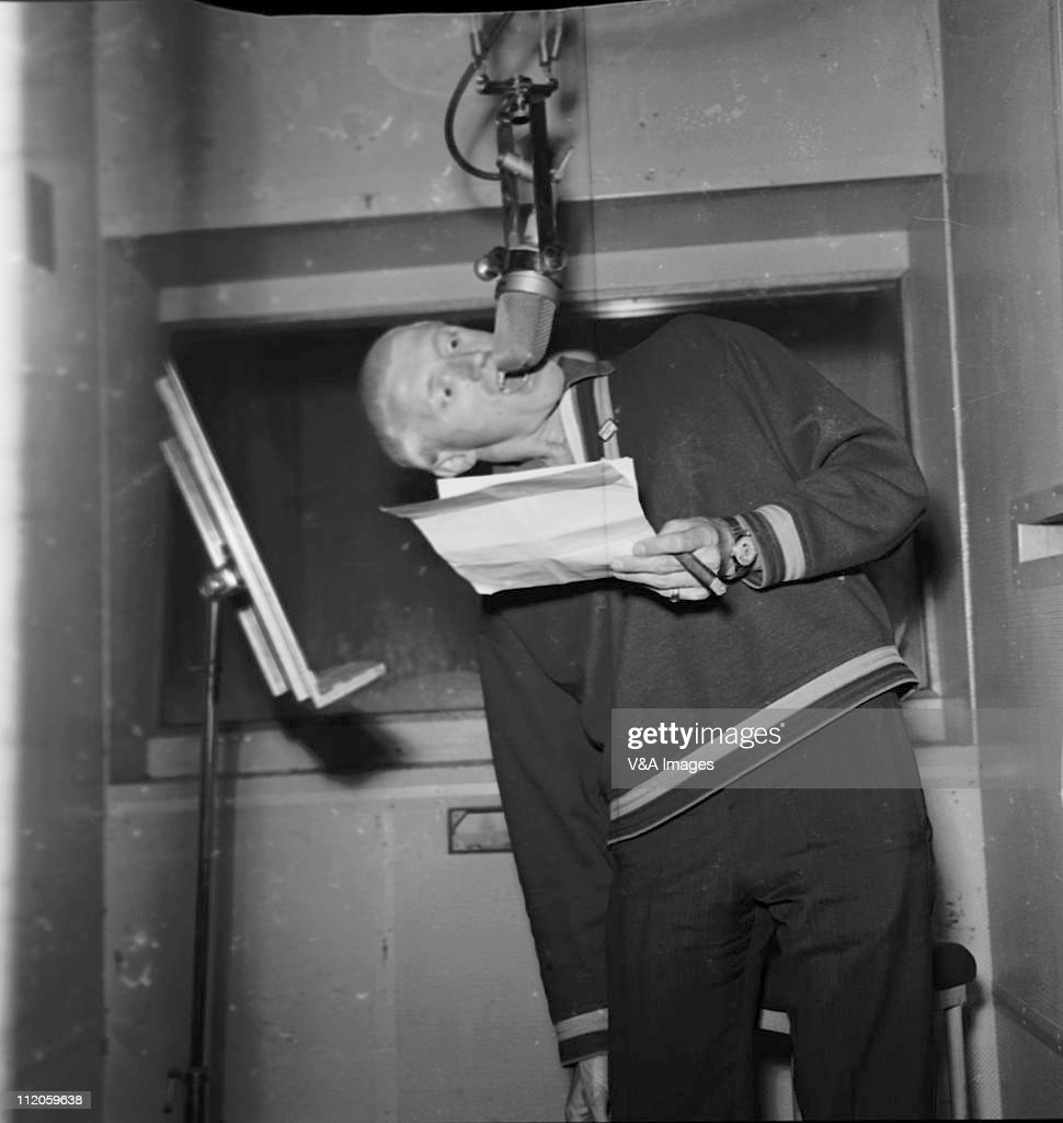 Jimmy Saville, posed, in recording studio, speaking into microphone upside down, 1963.
