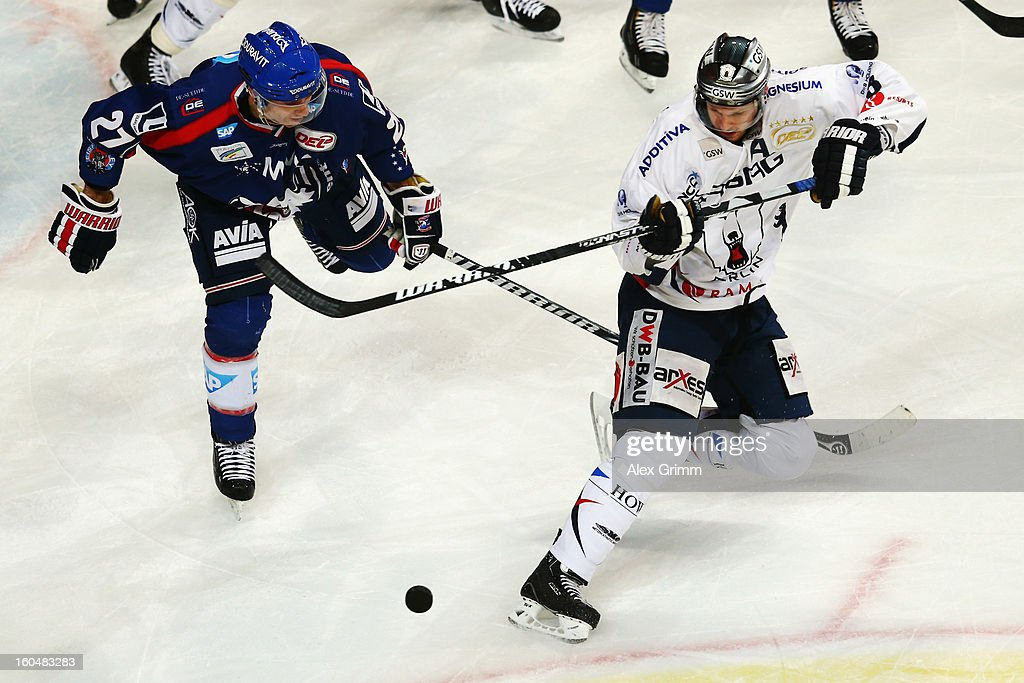 Jimmy Sharrow (R) of Berlin is challenged by Adam Mitchell of Mannheim during the DEL match between Adler Mannheim and Eisbaeren Berlin at SAP Arena on February 1, 2013 in Mannheim, Germany.