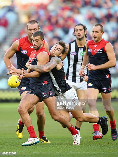 Jimmy Toumpas of the Demons kicks whilst being tackled by Jamie Elliott of the Magpies during the round 10 AFL match between the Melbourne Demons and...