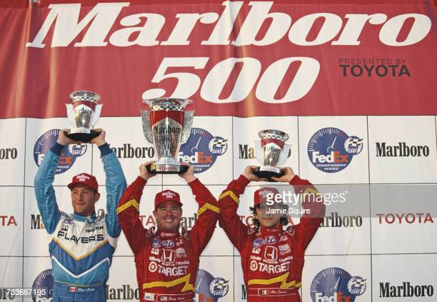 Jimmy Vasser of the United States driver of the Target Chip Ganassi Racing Reynard 98i Honda holds aloft his trophy alongside second placed team mate...
