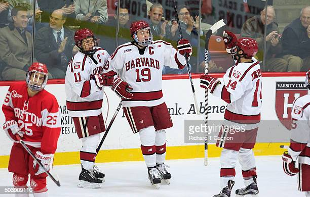 Jimmy Vesey of the Harvard Crimson celebrates his goal against the Boston University Terriers with his teammates Kyle Criscuolo and Alexander Kerfoot...
