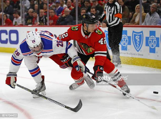 Jimmy Vesey of the New York Rangers and Gustav Forsling of the Chicago Blackhawks battle for position on the puck at the United Center on November 15...