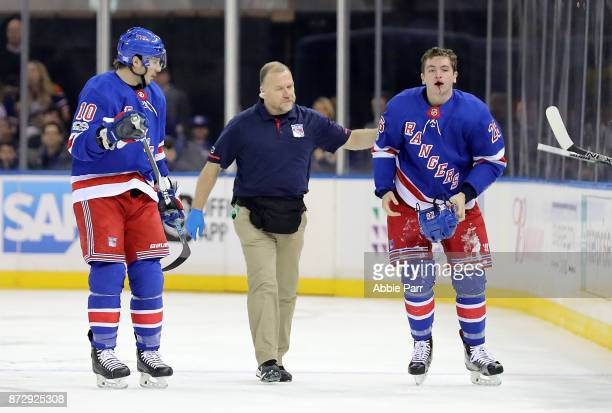 Jimmy Vesey of the New York Rangers leaves the ice after taking a skate to the face in the second period against the Edmonton Oilers during their...