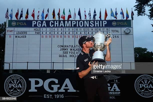 Jimmy Walker of the United States celebrates with the Wanamaker Trophy in front of the leaderboard after winning the 2016 PGA Championship at...