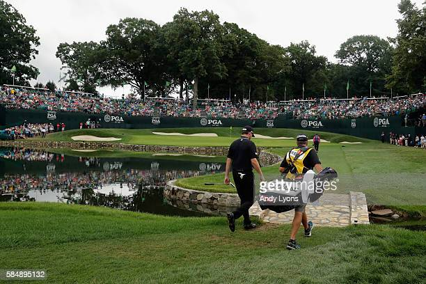 Jimmy Walker of the United States walks to the fourth green with caddie Andy Sanders during the final round of the 2016 PGA Championship at Baltusrol...