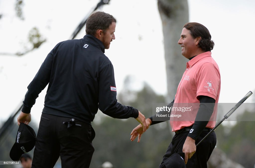 Jimmy Walker shakes hands with Pat Perez on the 18th hole during a continuation of the second round at the Genesis Open at Riviera Country Club on February 18, 2017 in Pacific Palisades, California.