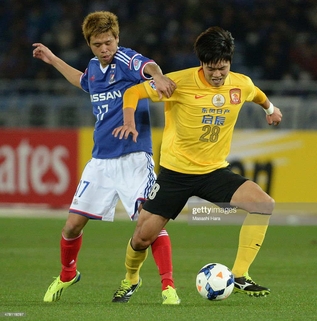Jin Hanato #17 of Yokohama F.Marinos (L) and Kim Younggwon #28 of Guangzhou Evergrande compete for the ball during the AFC Champions League Group G match between Yokohama F.Marinos and Guangzhou Evergrande at Nissan Stadium on March 12, 2014 in Yokohama, Japan.