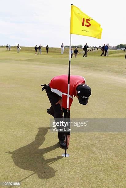 Jin Jeong of Korea retrieves his ball from the hole after an eagle on the 15th hole during his Quarter Final match against Paul Cutler of Northern...