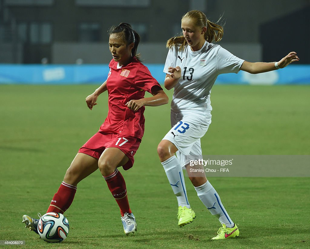 Jin Kun of China battles with Tamara of Slovakia during the 2014 FIFA Girls Summer Youth Olympic Football Tournament Semi Final match between China and Slovakia at Wutaishan Stadium on August 23, 2014 in Nanjing, China.