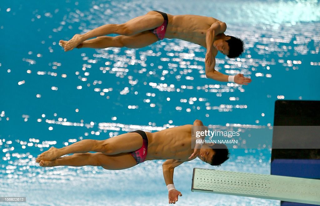 Jin Lin and Su Zewan of China perform in the men's synchronised 3m springboard diving comptition at the 9th Asian Swimming Championships in Dubai, on November 22, 2012. China won the gold medal in the event. AFP PHOTO/MARWAN NAAMANI