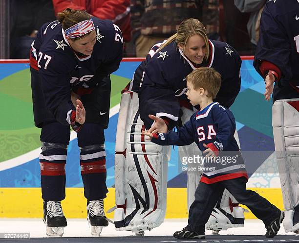 Jinelle ZauggSiergiej and Brianne Mclaughlin of the United States greet a teammates family member after receiving their silver medals during the ice...