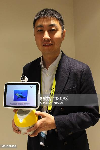 Jing Kun general manager of operating system DuerOS powering a new Baidu digital valet shows off the Little Fish home assistant unit at the 2017...