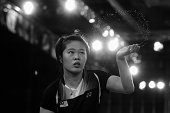 Jing Yi Tee of Malaysia flicks away sweat as she competes in her women's singles badminton quarterfinal match at Emirates Arena during day nine of...