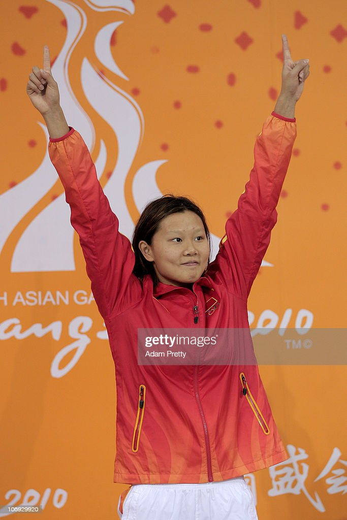 Jing Zhao of China celebrates prior to receiving the gold medal won in the Women's 100m Backstroke at the Aoti Aquatics Centre during day five of the 16th Asian Games Guangzhou 2010 on November 17, 2010 in Guangzhou, China.