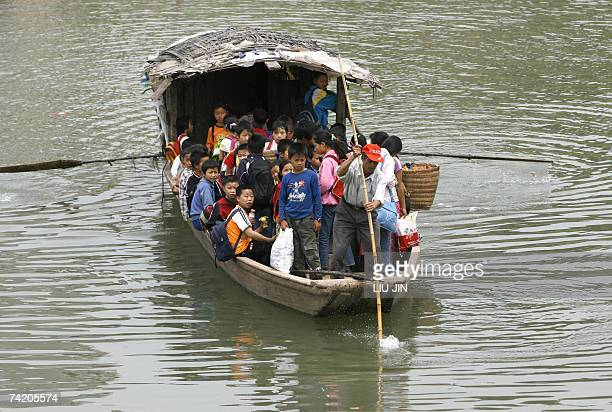 Schoolchildren commute on a ferry from their schools to their homes in Jinhua village in southwest China's Sichuan province 17 May 2007 China has...