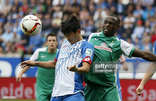 JinSu Kim of Hoffenheim and Anthony Ujah of Bremen compete for the ball during the Bundesliga match between 1899 Hoffenheim and SV Werder Bremen at...