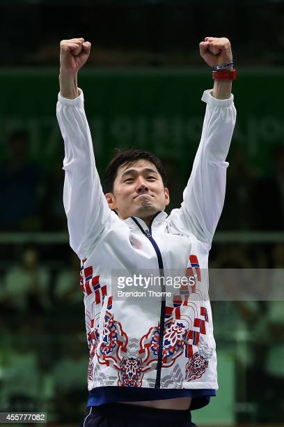 Jinsun Jung of South Korea celebrates atop the podium after winning gold in the Men's Epee Final during day one of the 2014 Asian Games at Goyang...