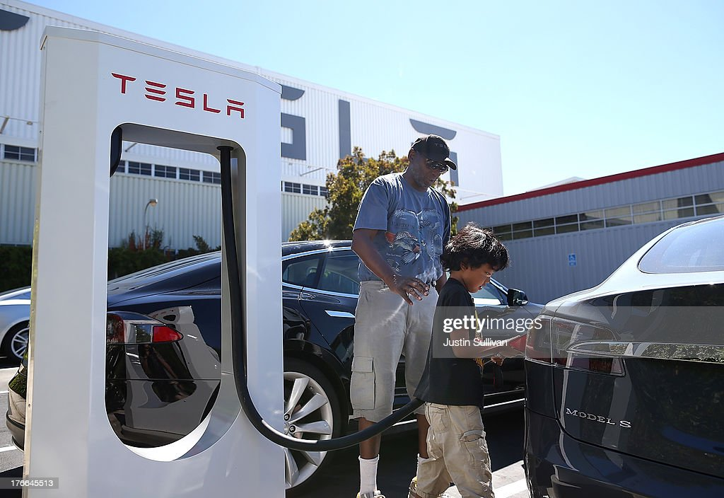 Jinyao Desandies (R) and Dandre Desandies (L) plug the Tesla Supercharger into their Tesla Model S sedan outside of the Tesla Factory on August 16, 2013 in Fremont, California. Tesla Motors opened a new Supercharger station with four stalls for public use at their factory in Fremont, California. The Superchargers allow owners of the Tesla Model S to charge their vehicles in 20 to 30 minutes for free. There are now 18 charging stations in the U.S. with plans to open more in the near future.