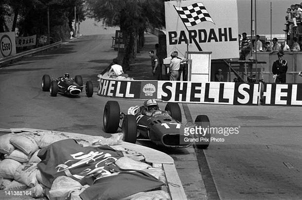 Jiohn Surtees of Great Britain drives the Scuderia Ferrari Ferrari 312/66 Ferrari V12 ahead of eventual race winner Jackie Stewart driving the Owen...