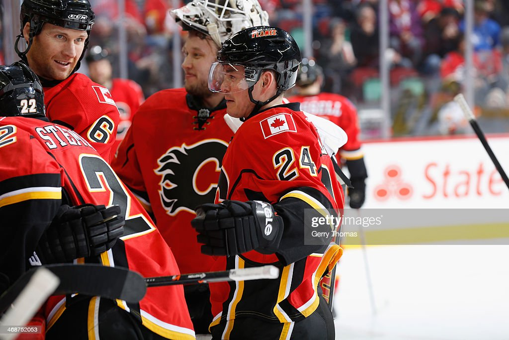 Jiri Hudler #24, Dennis Wideman #6 and Karri Ramo #31 of the Calgary Flames at the bench in a game against the San Jose Sharks at Scotiabank Saddledome on January 30, 2014 in Calgary, Alberta, Canada.