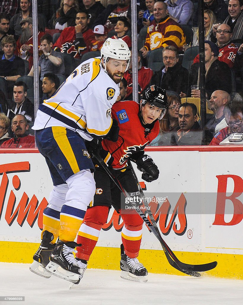 <a gi-track='captionPersonalityLinkClicked' href=/galleries/search?phrase=Jiri+Hudler&family=editorial&specificpeople=2118675 ng-click='$event.stopPropagation()'>Jiri Hudler</a> #24 of the Calgary Flames gets checked by <a gi-track='captionPersonalityLinkClicked' href=/galleries/search?phrase=Shea+Weber&family=editorial&specificpeople=554412 ng-click='$event.stopPropagation()'>Shea Weber</a> #6 of the Nashville Predators during an NHL game at Scotiabank Saddledome on March 21, 2014 in Calgary, Alberta, Canada. The Predators defeated the Flames 6-5.