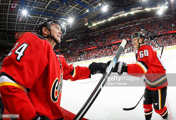 Jiri Hudler of the Calgary Flames high fives teammate Markus Granlund after a goal against the Toronto Maple Leafs at Scotiabank Saddledome on...