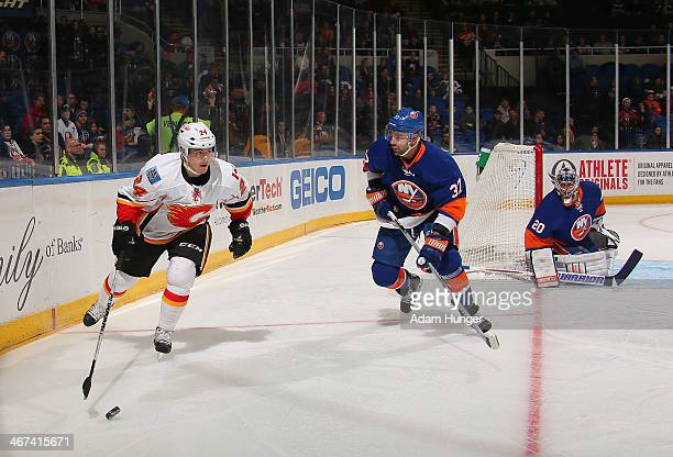 Jiri Hudler of the Calgary Flames looks to pass in front of Brian Strait and Evgeni Nabokov of the New York Islanders during the first period at...