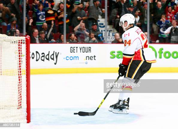 Jiri Hudler of the Calgary Flames retrieves the puck after the Vancouver Canucks got credit for a goal against the Flames on a delayed Vancouver...