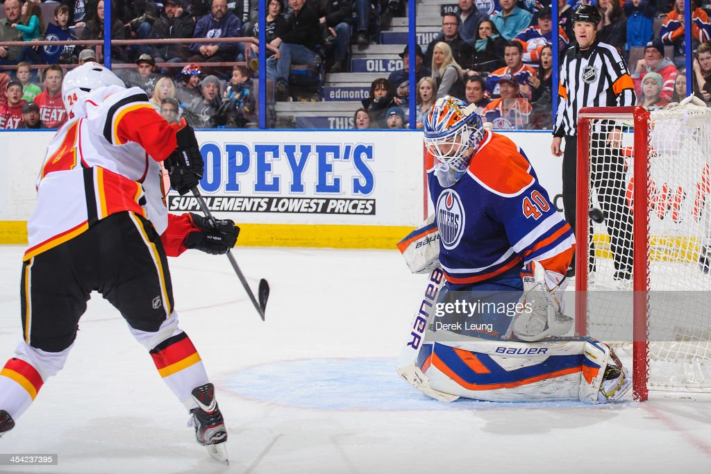 Jiri Hudler of the Calgary Flames scores the gamewinning goal on Devan Dubnyk of the Edmonton Oilers during an NHL game at Rexall Place on December 7...