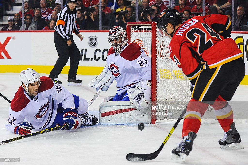 Jiri Hudler #24 of the Calgary Flames takes a shot as Mike Weaver #43 (L) and Carey Price #31 of the Montreal Canadiens defend during an NHL game at Scotiabank Saddledome on October 28, 2014 in Calgary, Alberta, Canada.